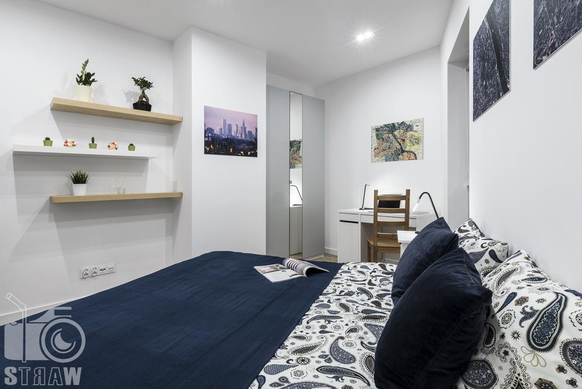 Sesje zdjęciowe apartamentów na wynajem krótkoterminowy, fotografia wnętrz Warszawa, sypialnia, łóżko dwuosobowe, półki, biurko, krzesło.