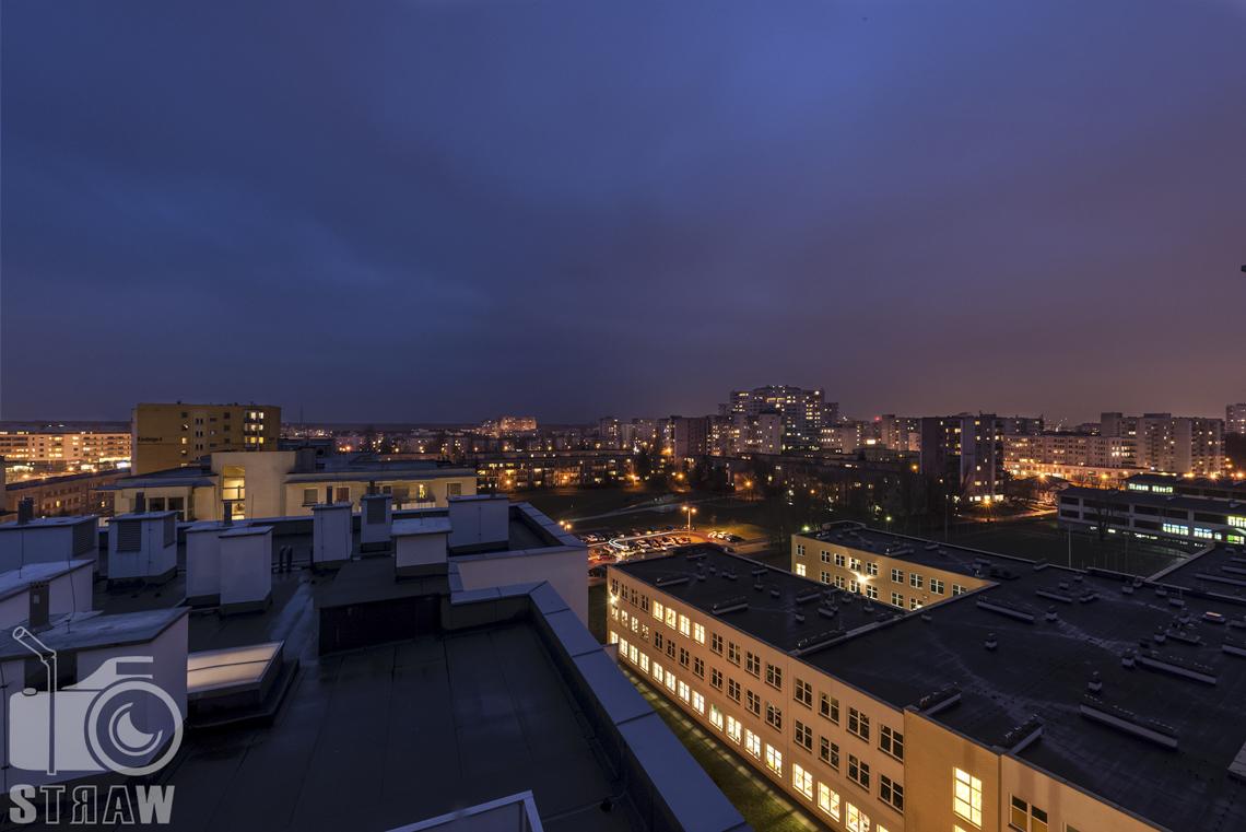 Sesje zdjęciowe apartamentów na wynajem krótkoterminowy, fotografia wnętrz Warszawa, widok z balkonu na oświetloną wieczorną Warszawę.
