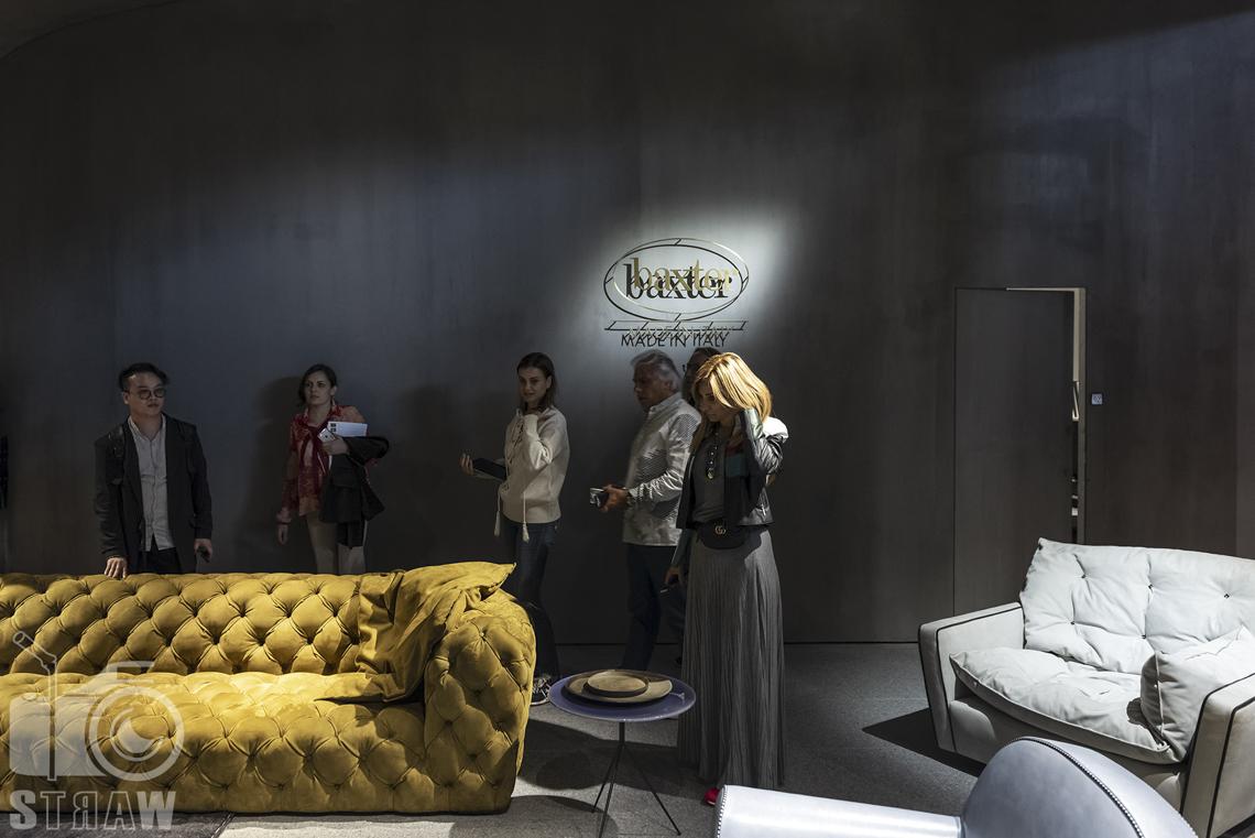 Fotorelacje, targi, zdjęcia z targów Salone del Mobile Milano, Baxter, kanapa żółta, fotel dwuosobowy szary. ludzie oglądający wystawę.