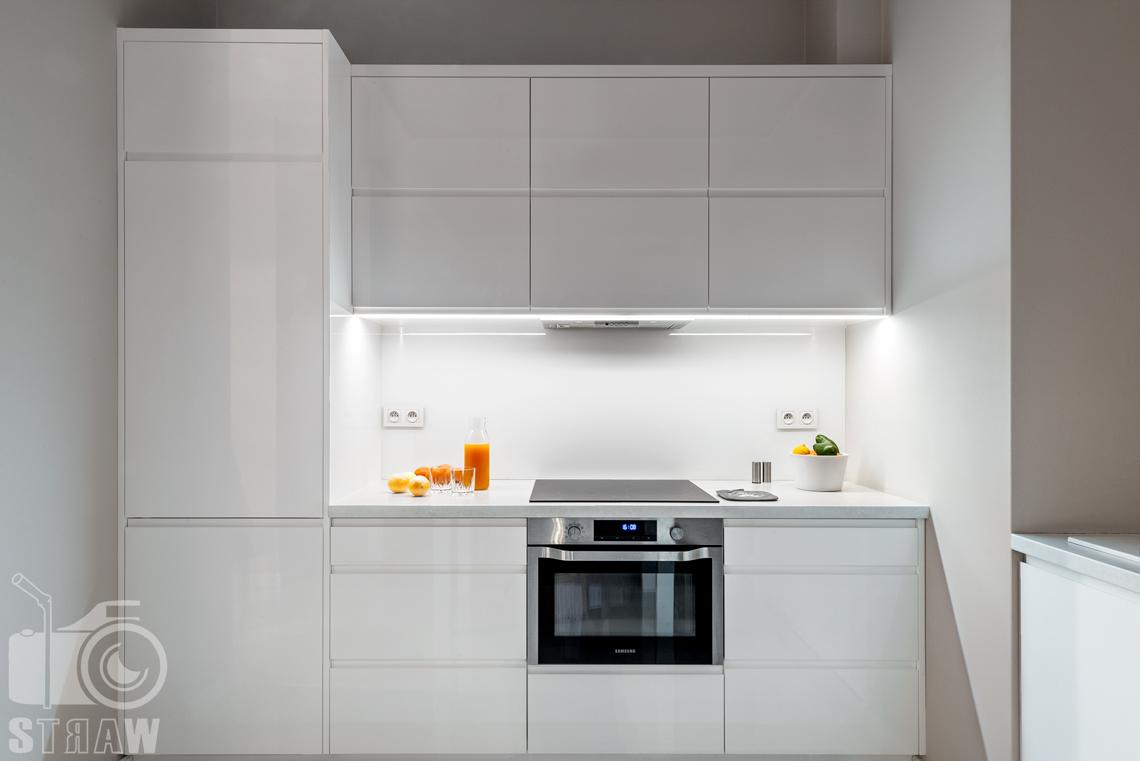 Fotografia apartamentów na wynajem krótko i długoterminowy, zdjęcie kuchni z białą zabudową.