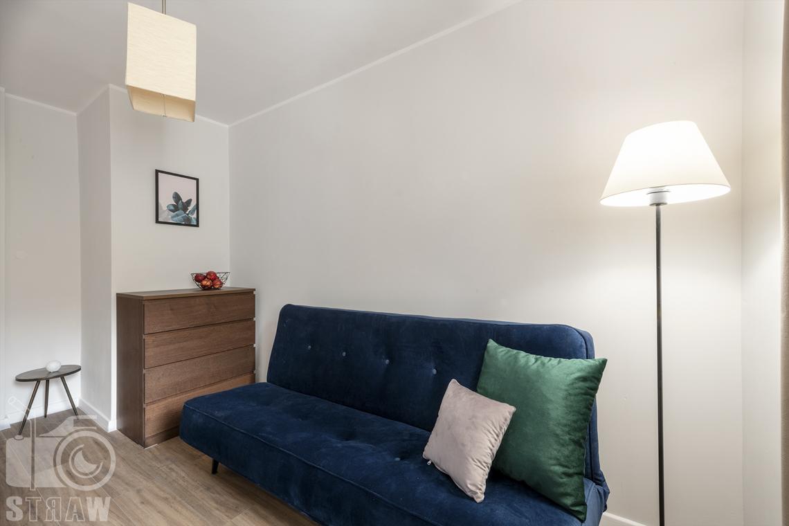 Fotografia nieruchomości na wynajem Warszawa, zdjęcie pokoju z sofą i komodą.