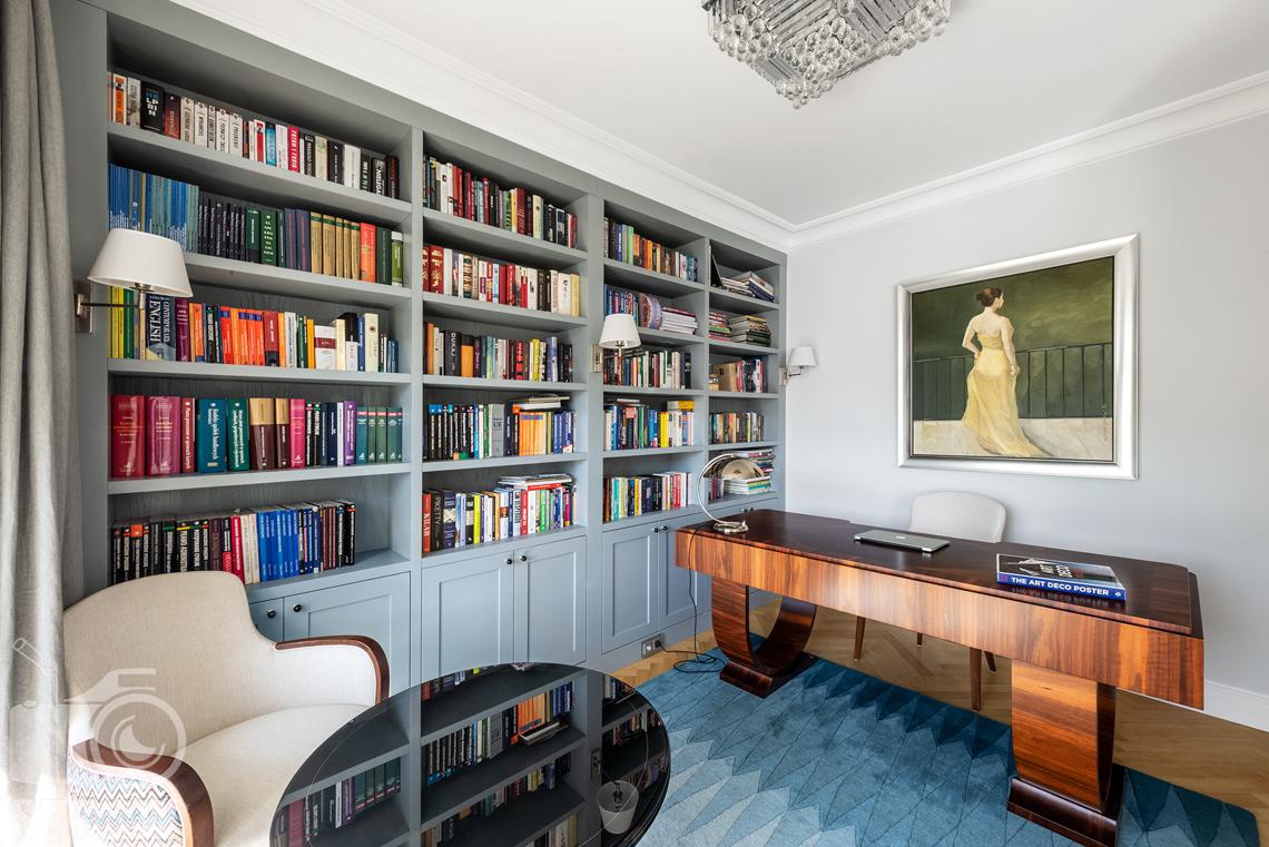 Fotografia wnętrz nieruchomości na sprzedaż w Warszawie, na zdjęciu gabinet z biblioteczką.