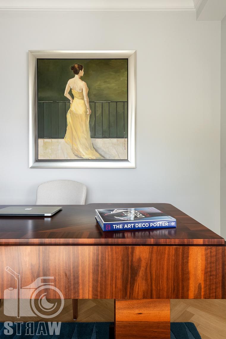 Fotografia wnętrz nieruchomości na sprzedaż, biurko i obraz w gabinecie.