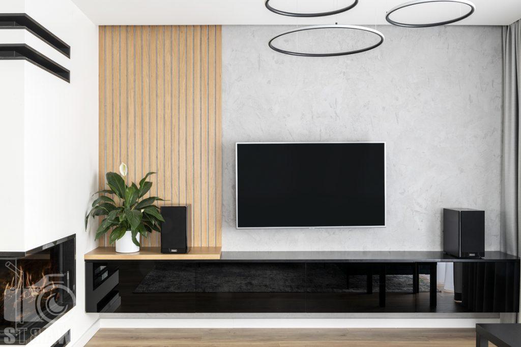 Fotografia wnętrz dla producenta zabudowy firmy Kittchen, na zdjęciu salon z wykonaną szafką w połysku i wykonanymi lamelami.