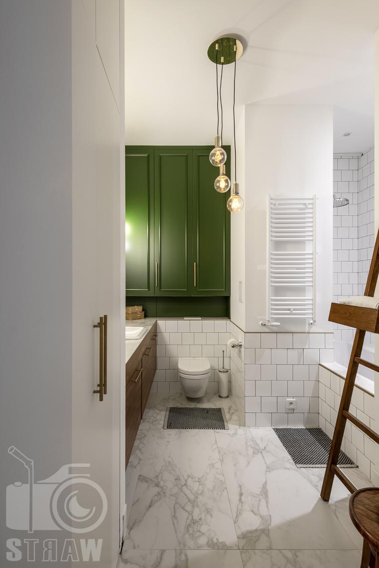 Fotografia wnętrz, zdjęcia, kamienica, łazienka, szafa, żyrandol z wiszącymi kulami, kaloryfer, szafki, WC, wanna.