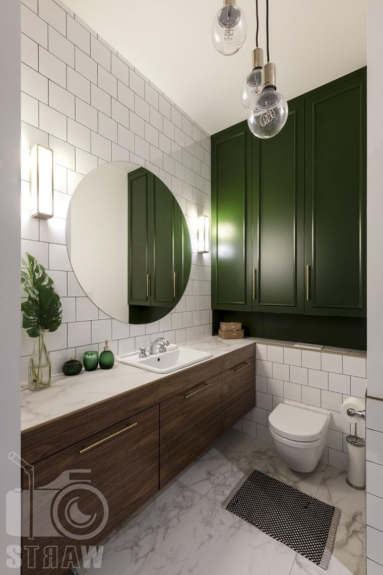 Fotografia wnętrz, zdjęcia, kamienica, łazienka, lustro, WC, szafka stojąca, umywalka, oświetlenie boczne, lampy wiszące.