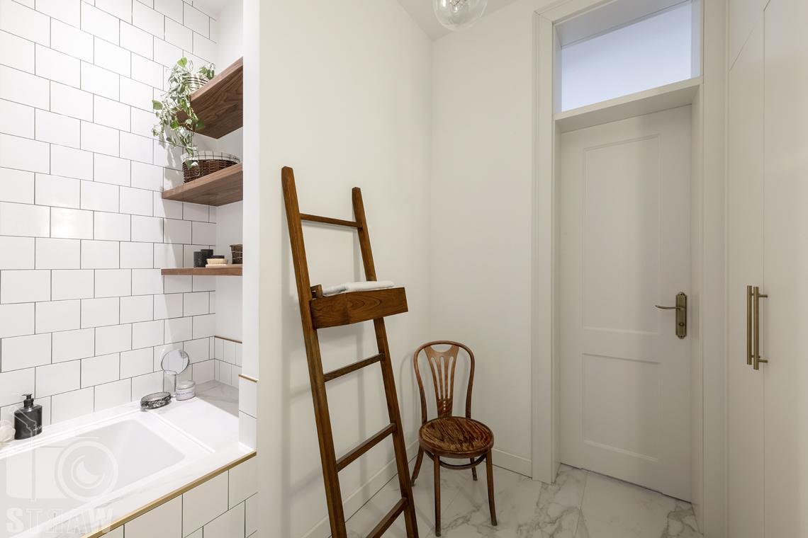 Fotografia wnętrz, zdjęcia, kamienica, łazienka, drzwi wejściowe, krzesło, drabinka, wanna, półki.