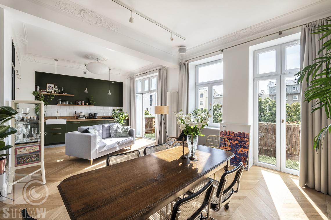 Fotografia wnętrz, zdjęcia, kamienica, salon, stół drewniany prostokątny, okna, kanapa, aneks kuchenny.