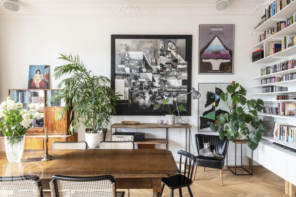 Fotografia wnętrz Warszawa, zdjęcia wnętrza mieszkania zlokalizowanego w kamienicy, ujęcie prezentujące część salonu ze stołem i biblioteczką.