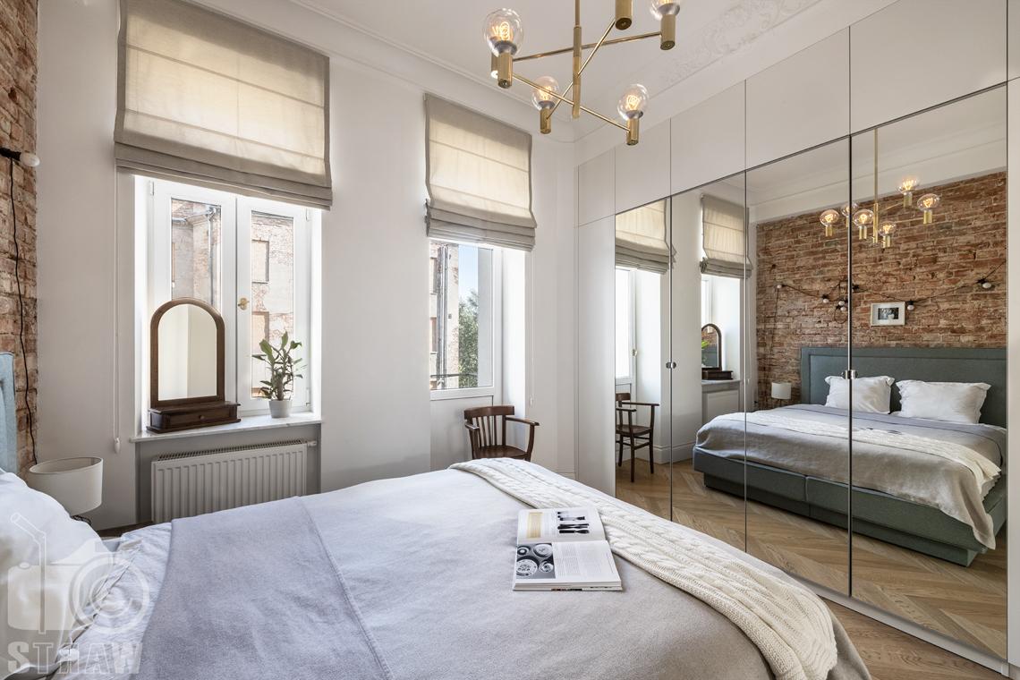 Fotografia wnętrz, zdjęcia, kamienica, sypialnia, łóżko dwuosobowe, lustro, krzesło, okna, żyrandol.