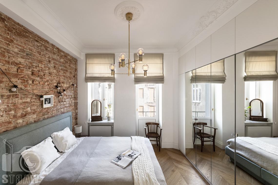 Fotografia wnętrz, zdjęcia, kamienica, sypialnia, sztukateria na suficie, łóżko dwuosobowe, lustro, żyrandol, krzesło.