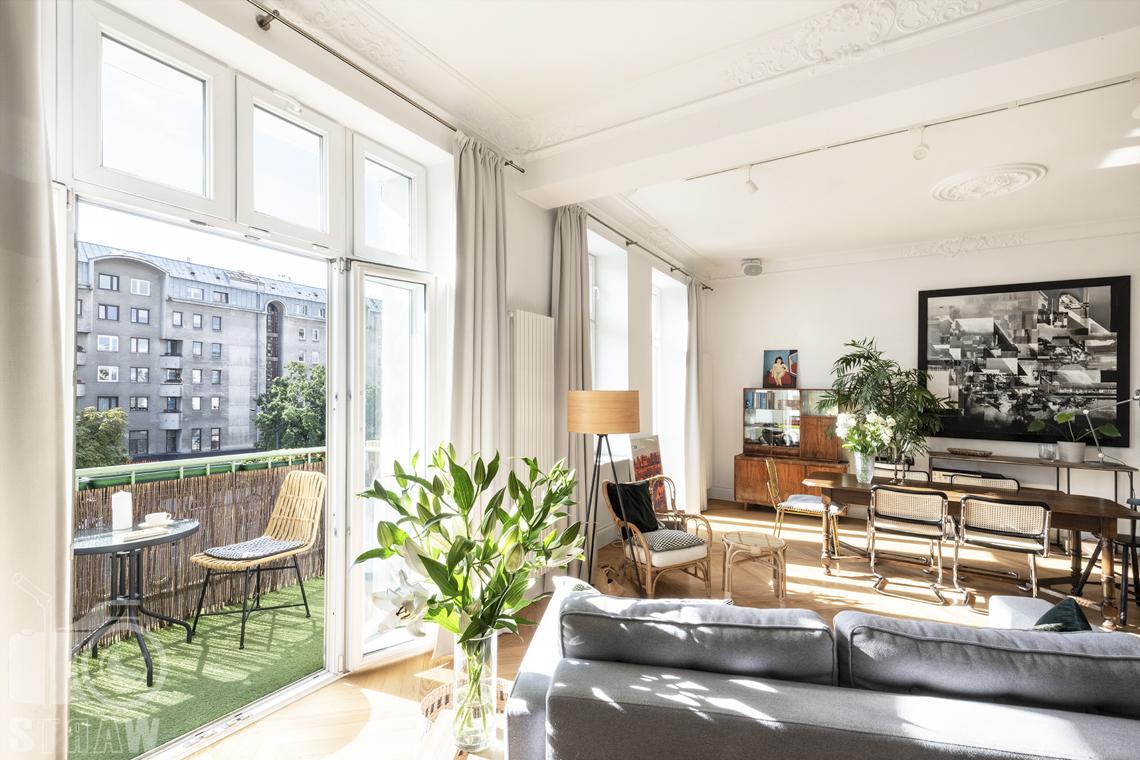 Fotografia wnętrz, zdjęcia, kamienica, salon, kanapa, lampa stojąca, fotel, obraz, balkon, stół kawowy, krzesło.