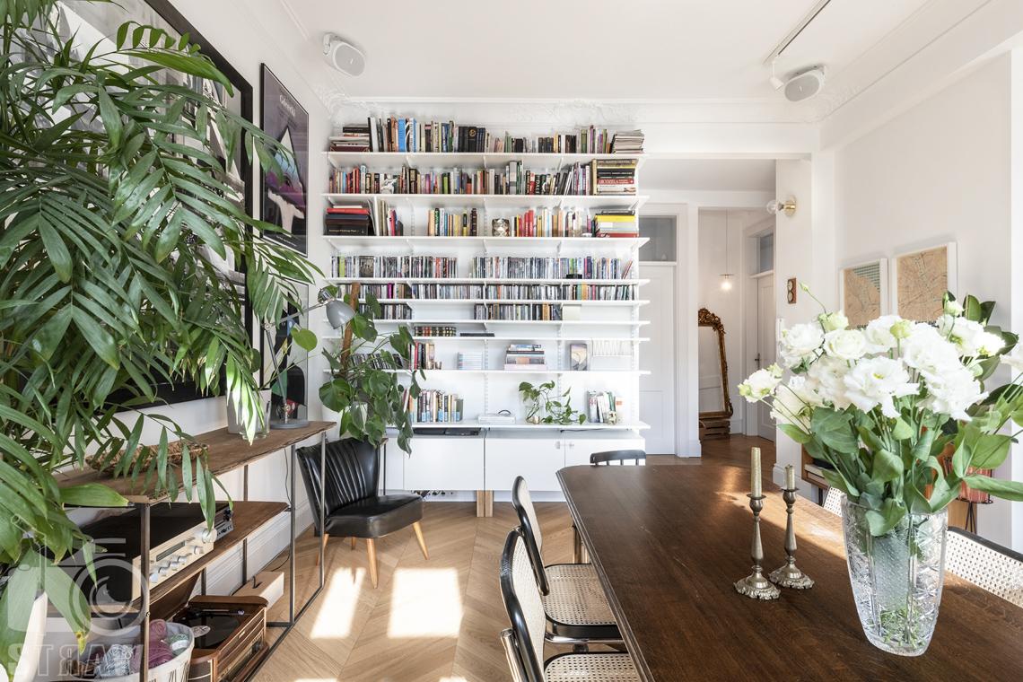 Fotografia wnętrz, zdjęcia, kamienica, salon, biblioteczka, stół, krzesła, kwiaty w wazonie, fotel, regał.