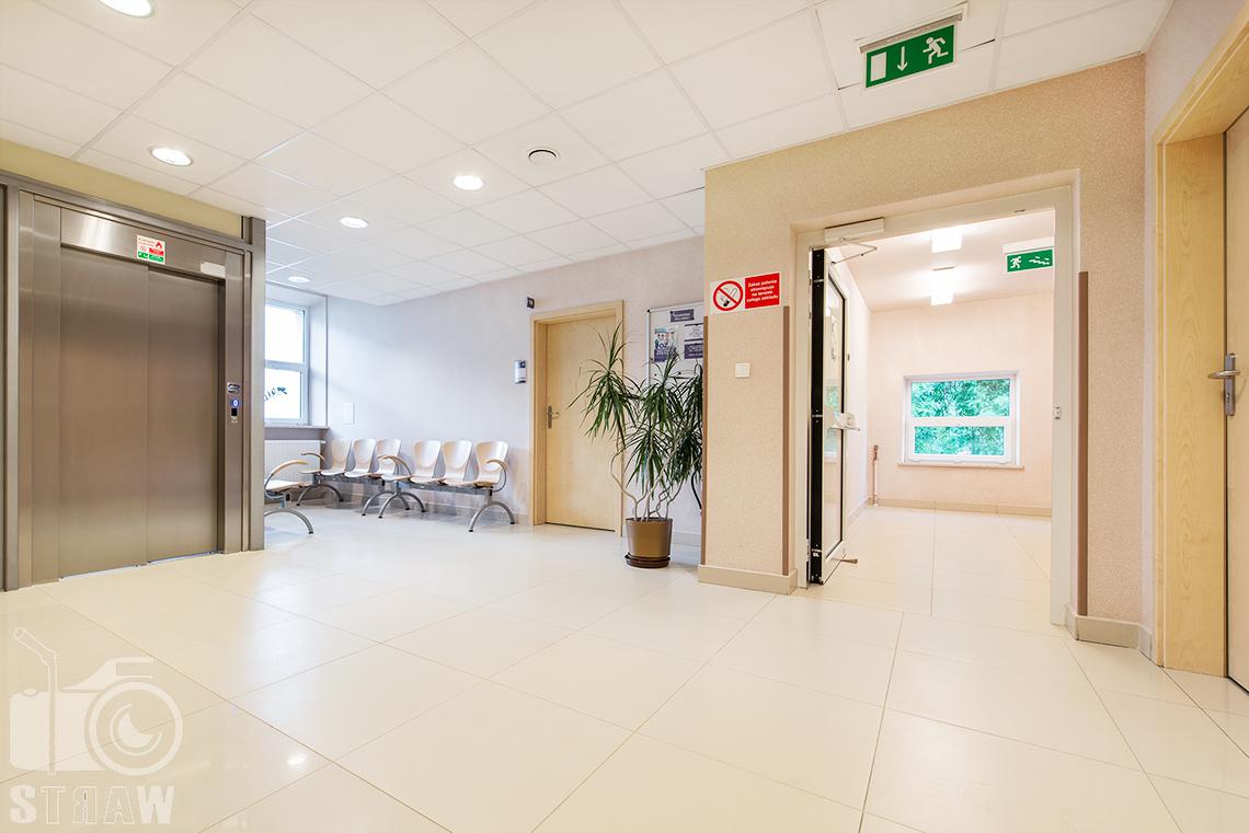 Fotografia wnętrz przychodni specjalistycznej publicznego zakładu opieki zdrowotnej wola-śródmieście przy ulicy Dragonów w Warszawie, korytarz i poczekalnia.