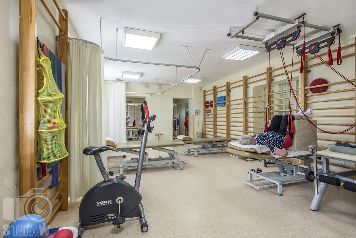 Zdjęcia wnętrz przychodni specjalistycznej publicznego zakładu opieki zdrowotnej wola-śródmieście przy ulicy Ciołka w Warszawie, sala ćwiczeń i osoba w trakcie rehabilitacji.