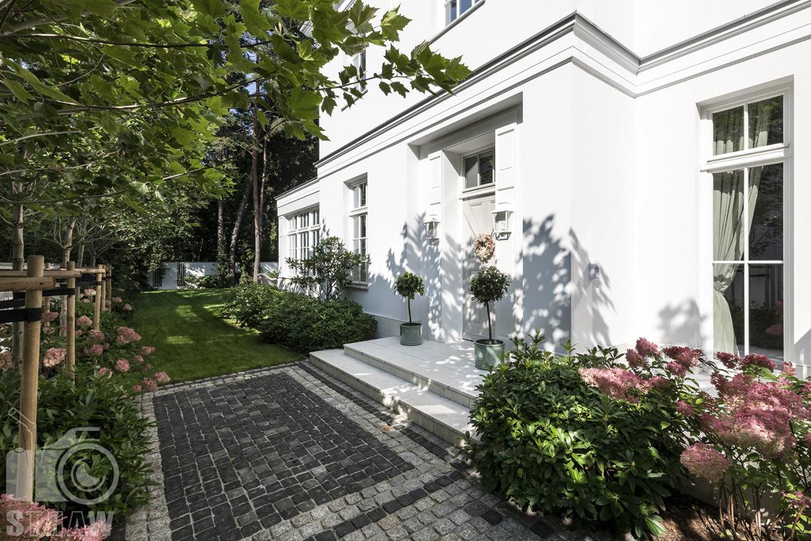 Fotograf nieruchomości Warszawa, wejście do domu na sprzedaż w otoczeniu hortensji.