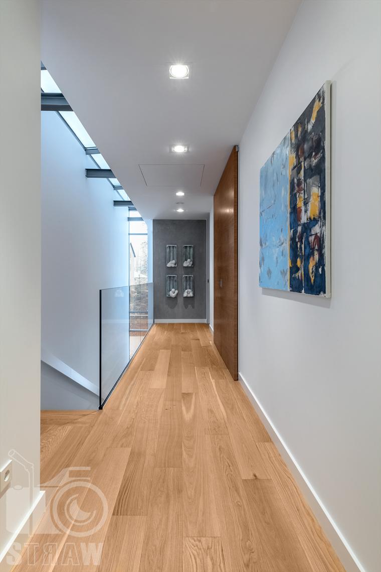 Fotografia wnętrz dla projektantów i architektów, hol na piętrze, obraz, przeszklona barierka i rzeźby naścienne.