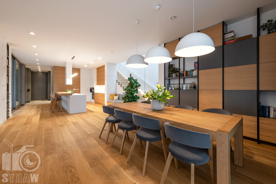 Fotografia wnętrz dla projektantów i architektów, salon i jadalnia z dużym stołem drewnianym, widok w stronę kuchni.