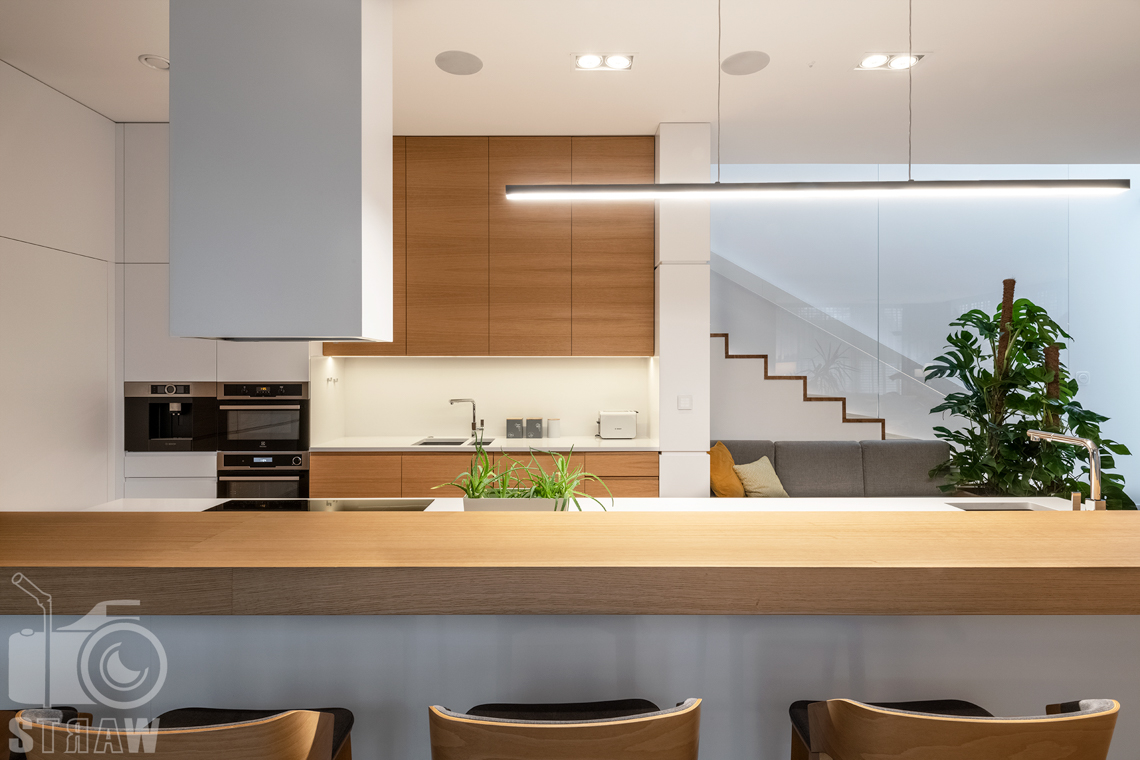Fotografia wnętrz dla projektantów i architektów, widok na kuchnię od strony wyspy kuchennej i stołków barowych.