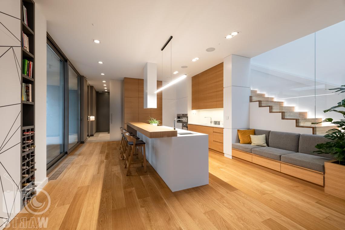 Fotografia wnętrz dla projektantów i architektów, otwarta kuchnia z wyspą i blatem do jedzenia oraz krzesłami barowymi.