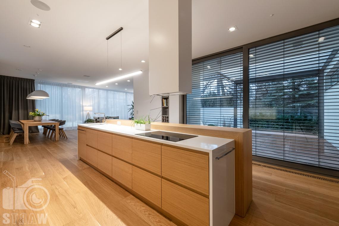 Fotografia wnętrz dla projektantów i architektów, widok z kuchni w stronę jadalni i salonu oraz przeszklonego tarasu.