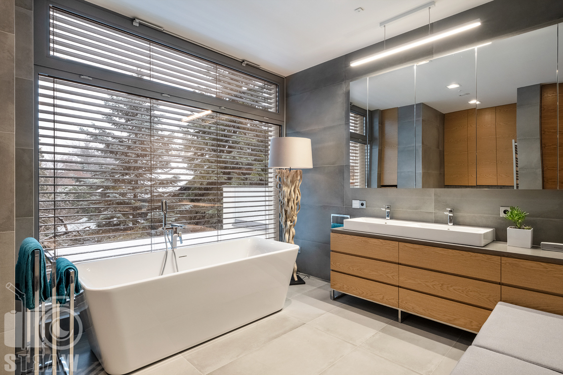 Fotografia wnętrz dla projektantów i architektów, łazienka z wolno stojącą wanną, dużym oknem na całą ścianę i śniegiem za oknem.
