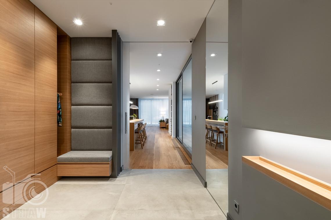 Fotografia wnętrz dla projektantów i architektów, przedpokój z szafami i siedziskiem, widok na kuchnię i jadalnię.