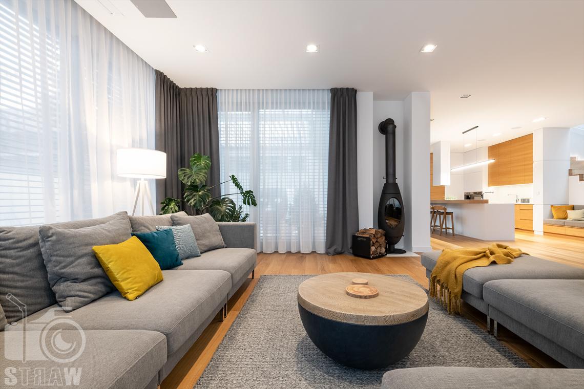 Fotografia wnętrz dla projektantów i architektów, salon z kominkiem, sofami i widokiem na kuchnię.