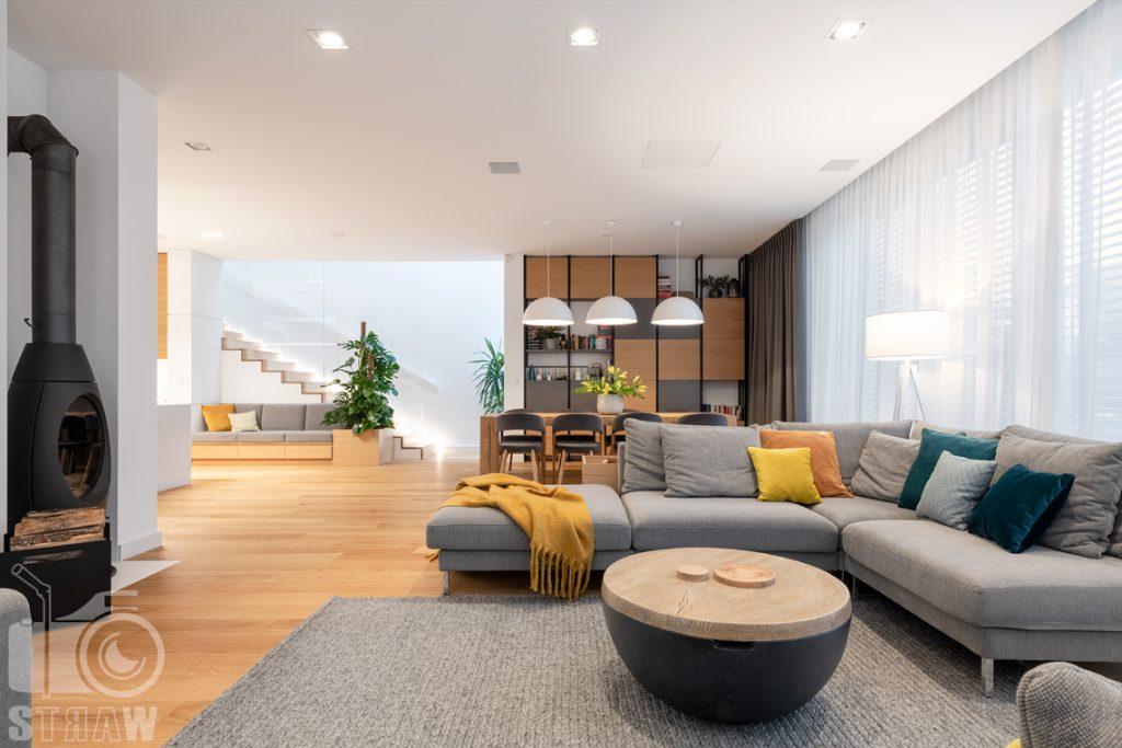 Fotografia wnętrz dla projektantów i architektów, kominek w salonie, stolik kawowy, sofy i jadalnia.