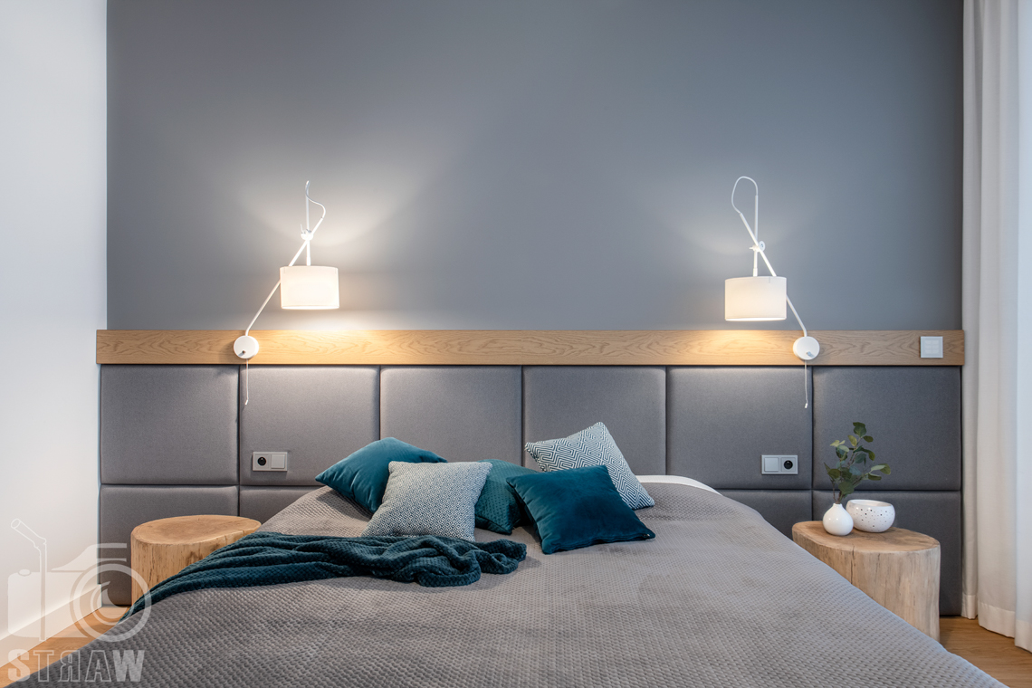 Fotografia wnętrz dla projektantów i architektów, łóżko w sypialni małżeńskiej z szafkami nocnymi z pni drzewa.