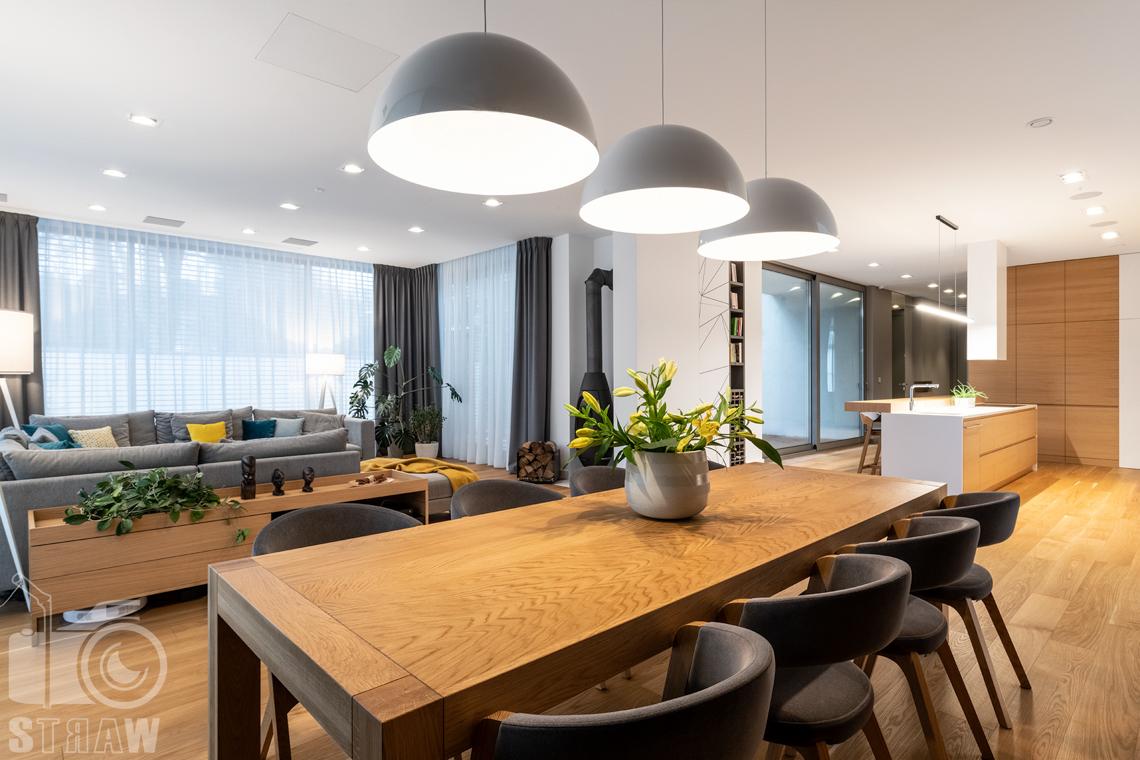 Fotografia wnętrz dla projektantów i architektów, jadalnia, stół z ośmioma krzesłami, widok w stronę salonu i sof oraz kominka.