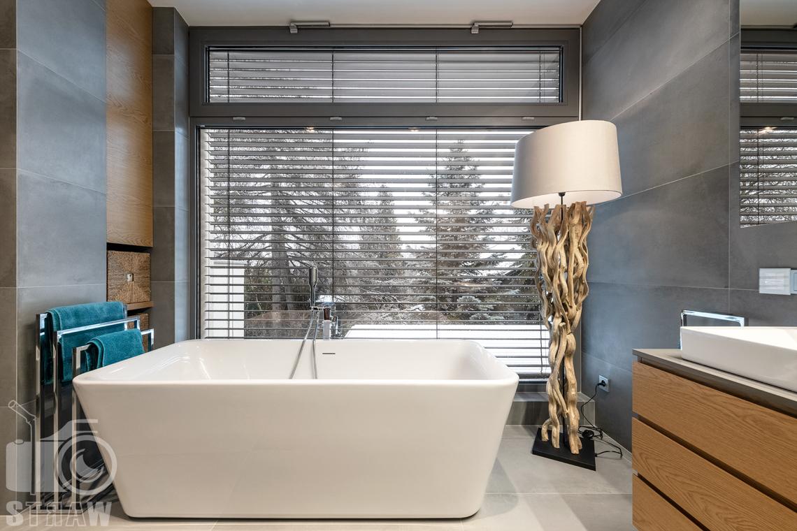 Fotografia wnętrz dla projektantów i architektów, duże okno w łazience, wanna wolno stojąca i lampa.