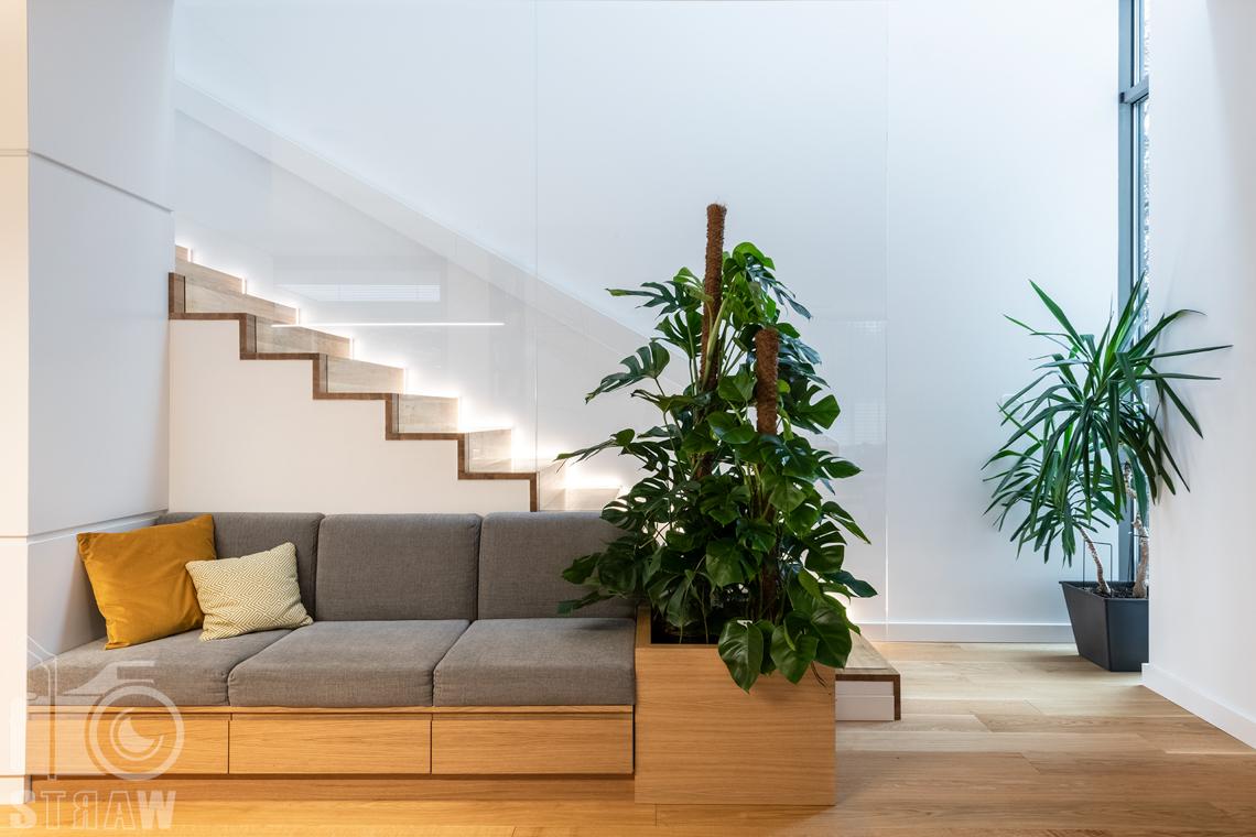 Zdjęcia wnętrz dla projektantów i architektów, sofa do siedzenia i odpoczynku usytuowana przy kuchni i klatce schodowej.