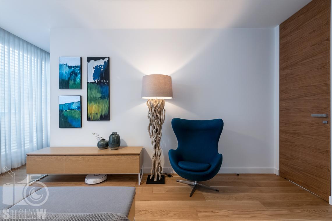 Zdjęcia wnętrz dla projektantów i architektów, fotel, lampa i obrazy w sypialni.