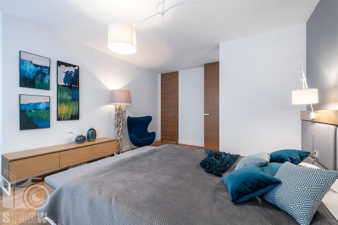 Zdjęcia wnętrz dla projektantów i architektów, sypialnia małżeńska z obrazami i fotelem.