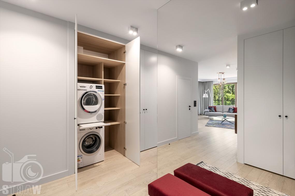 Fotografia wnętrz dla projektanta, zdjęcie przedpokoju z otwartymi szafami przeznaczonymi na pralkę.