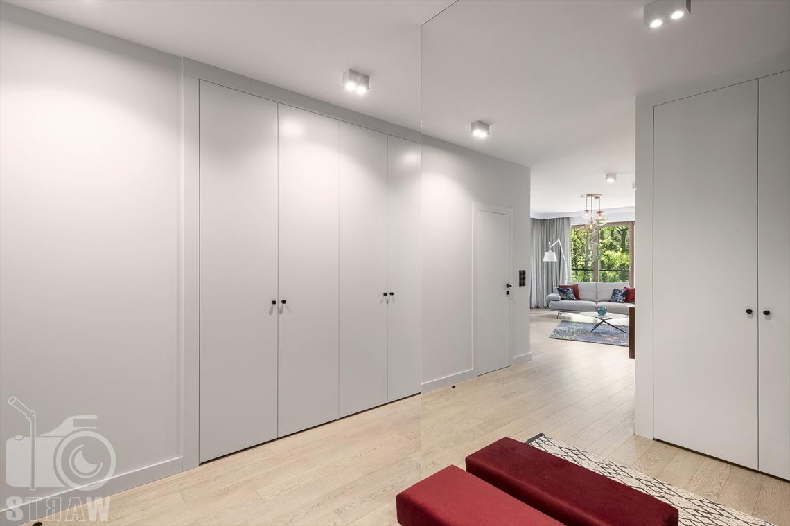 Fotografia wnętrz dla projektanta, zdjęcie przedpokoju z dużym lustrem i szafami.