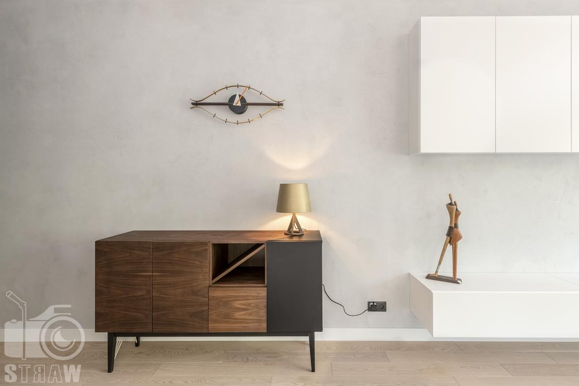 Fotografia wnętrz dla projektanta, zdjęcie komody z lampką na tle betonowej ściany.
