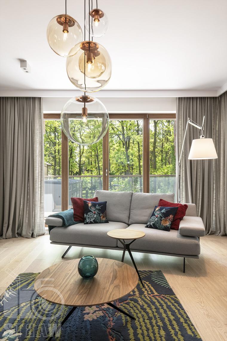 Zdjęcie salonu z wiszącymi szklanymi, kulistymi lampami.