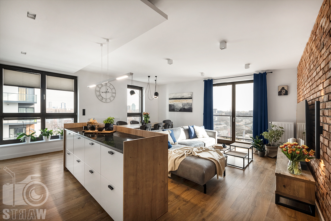 Fotografia wnętrz dla projektantów i architektów, salon z wyspą kuchenną i ceglaną ścianą.