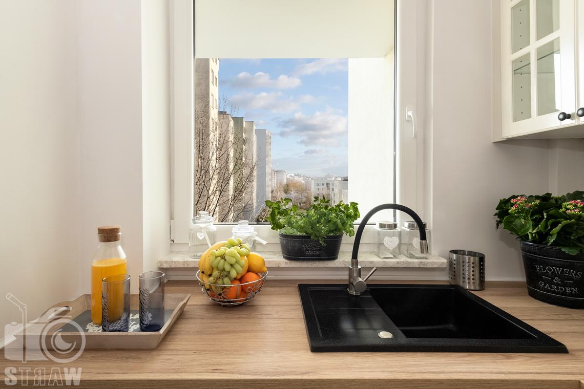 Sesja fotograficzna mieszkania na sprzedaż, zdjęcia nieruchomości po remoncie i w pełni wyposażonej, kuchnia, blat ze zlewem i okno.