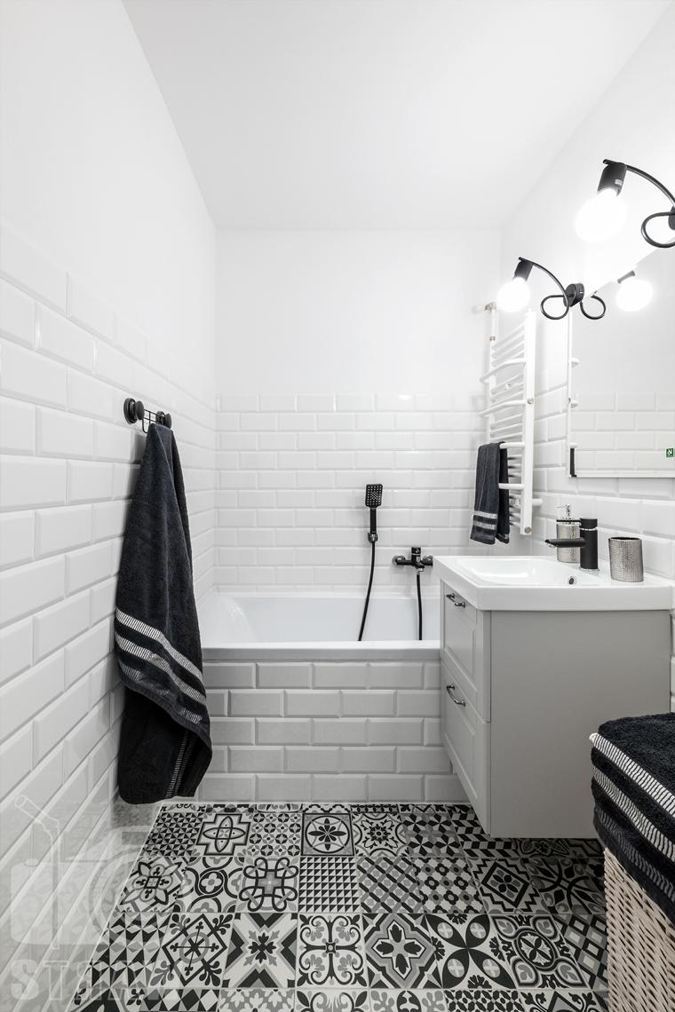 Sesja fotograficzna mieszkania na sprzedaż, zdjęcia nieruchomości po remoncie i w pełni wyposażonej, łazienka w kolorach białym i czarnym, wanna, umywalka.