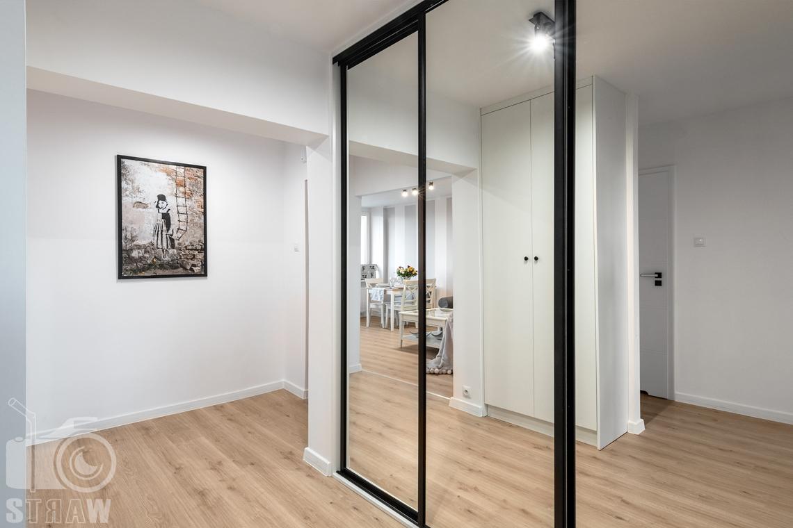 Sesja fotograficzna mieszkania na sprzedaż, zdjęcia nieruchomości po remoncie i w pełni wyposażonej, przedpokój, duża szafa z lustrami i widok na salon.