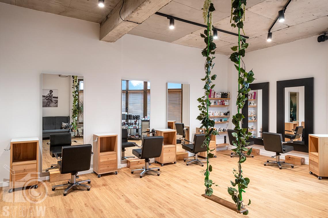 Sesja fotograficzna salonu fryzjerskiego, zdjęcia wnętrz komercyjnych, ujęcie wnętrza salonu z huśtawką zawieszoną po środku.