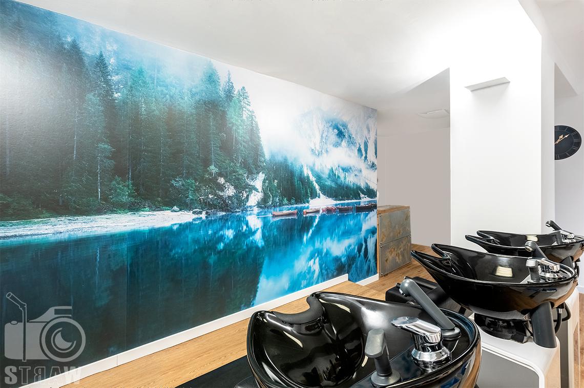 Sesja fotograficzna salonu fryzjerskiego, zdjęcia wnętrz komercyjnych, ujęcie myjek i ściany z fototapetą.
