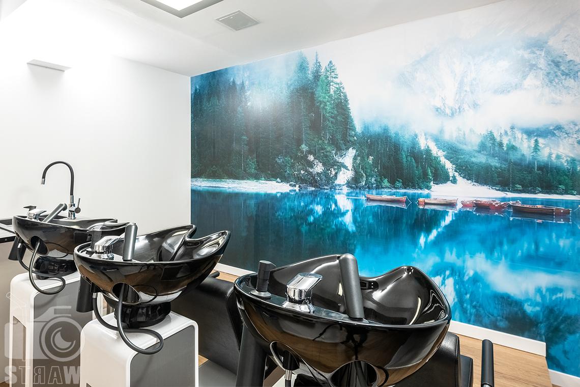 Sesja fotograficzna salonu fryzjerskiego, zdjęcia wnętrz komercyjnych, zdjęcie pomieszczenia z myjkami i fototapetą.