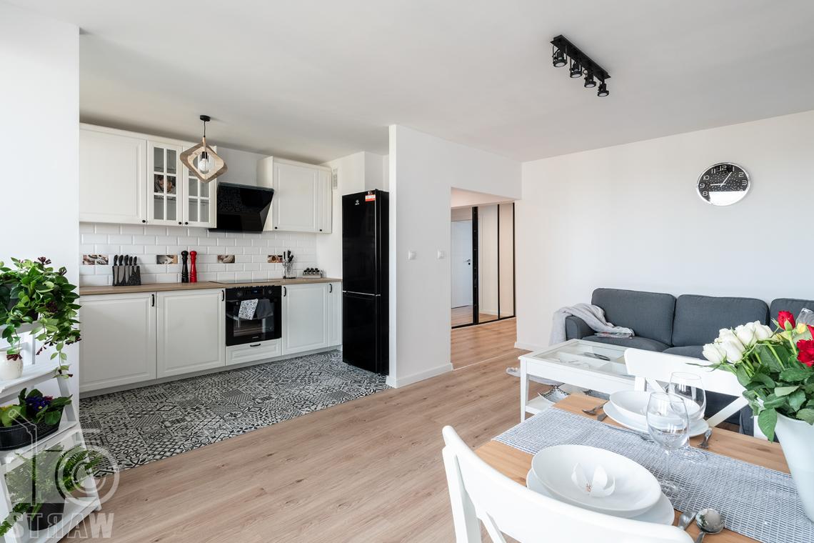 Sesja fotograficzna mieszkania na sprzedaż, zdjęcia nieruchomości po remoncie i w pełni wyposażonej, salon, jadalnia, stół, widok w stronę kuchni.