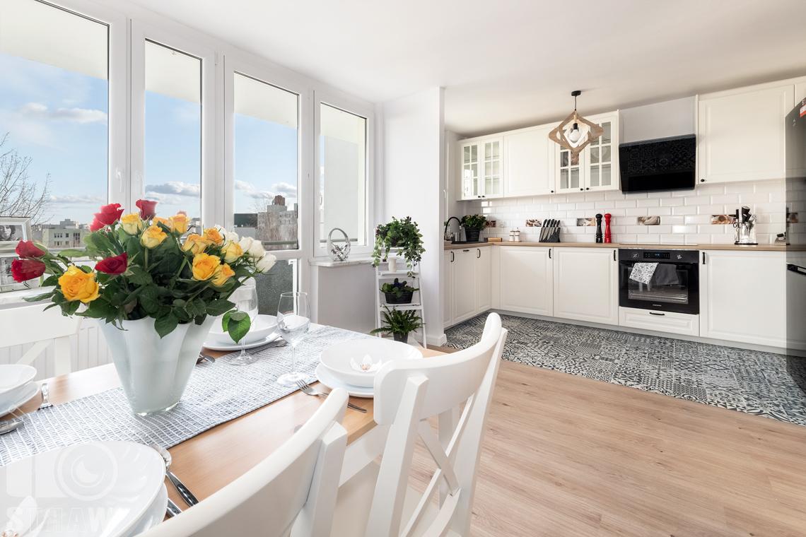 Sesja fotograficzna mieszkania na sprzedaż, zdjęcia nieruchomości po remoncie i w pełni wyposażonej, salon i kuchnia, stół w jadalni.