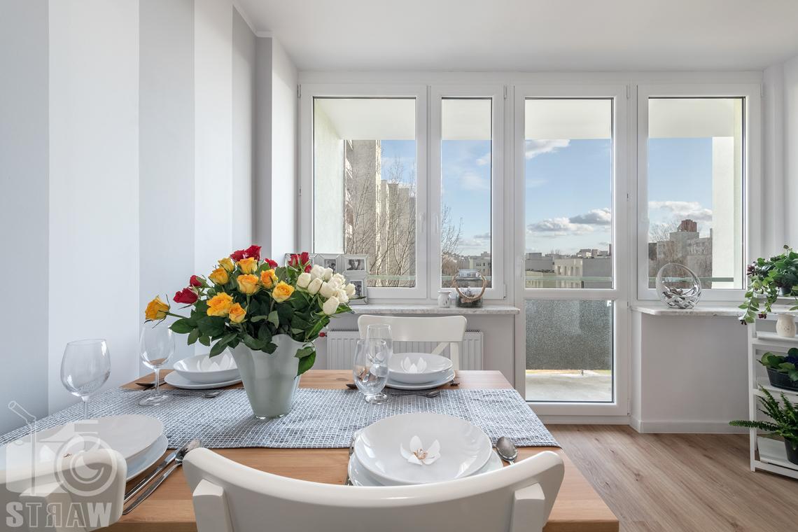 Sesja fotograficzna mieszkania na sprzedaż, zdjęcia nieruchomości po remoncie i w pełni wyposażonej, stół z kwiatami i widok na taras.