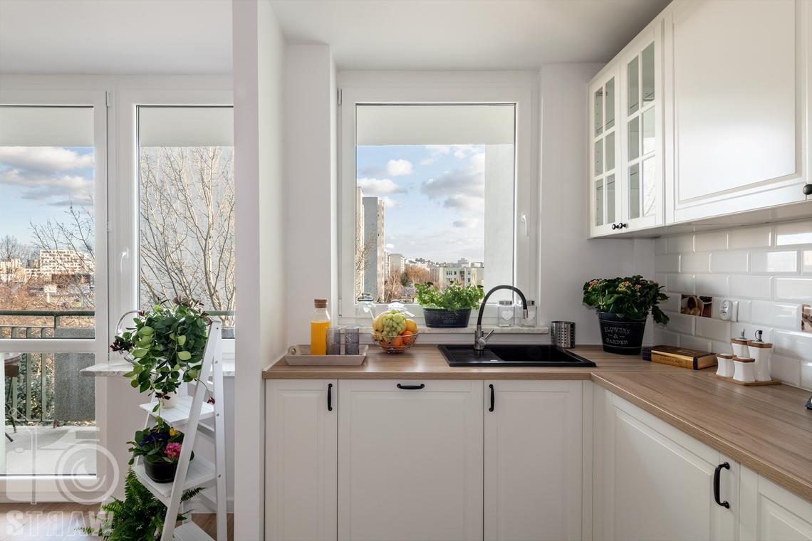 Sesja fotograficzna mieszkania na sprzedaż, zdjęcia nieruchomości po remoncie i w pełni wyposażonej, kuchnia, blaty i szafki, kwiaty w doniczkach.